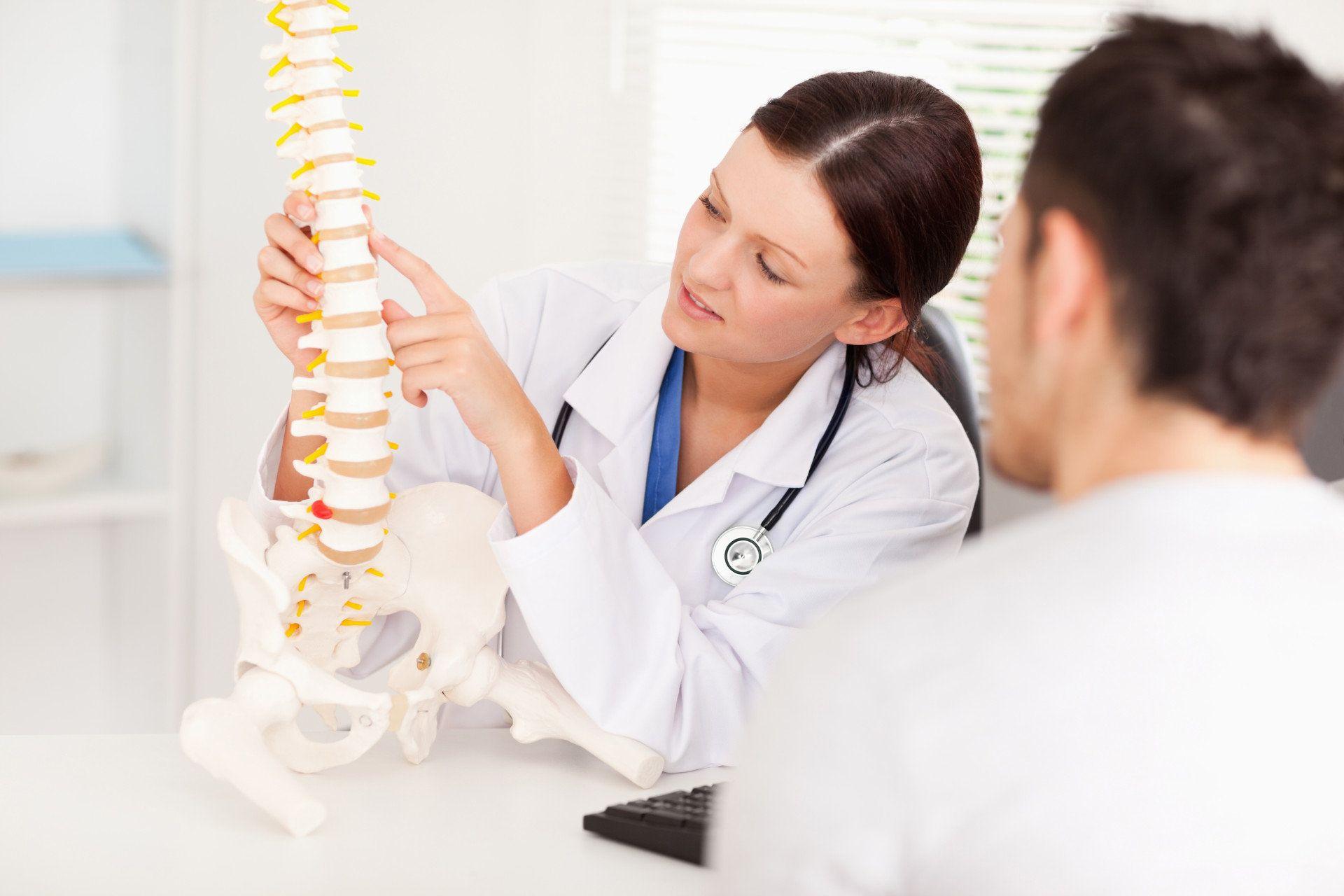 Ärztin erklärt Patient etwas an Wirbelsäulen-Skelett