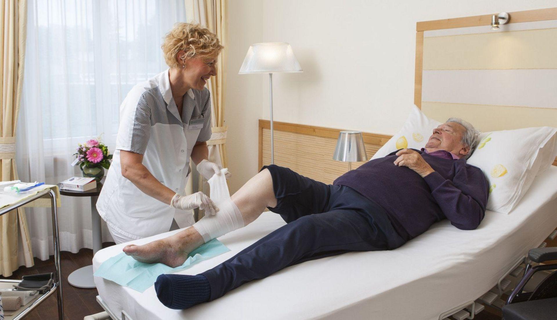 Spitex-Mitarbeiterin wechselt Verband am Bein eines Patienten