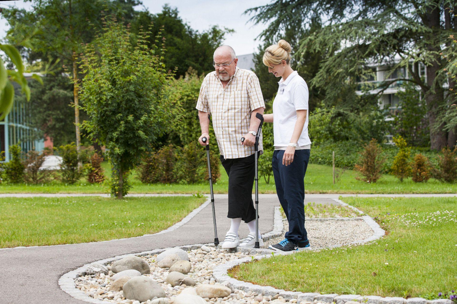 Patient und Physiotherapeutin laufen über Parcours im Park
