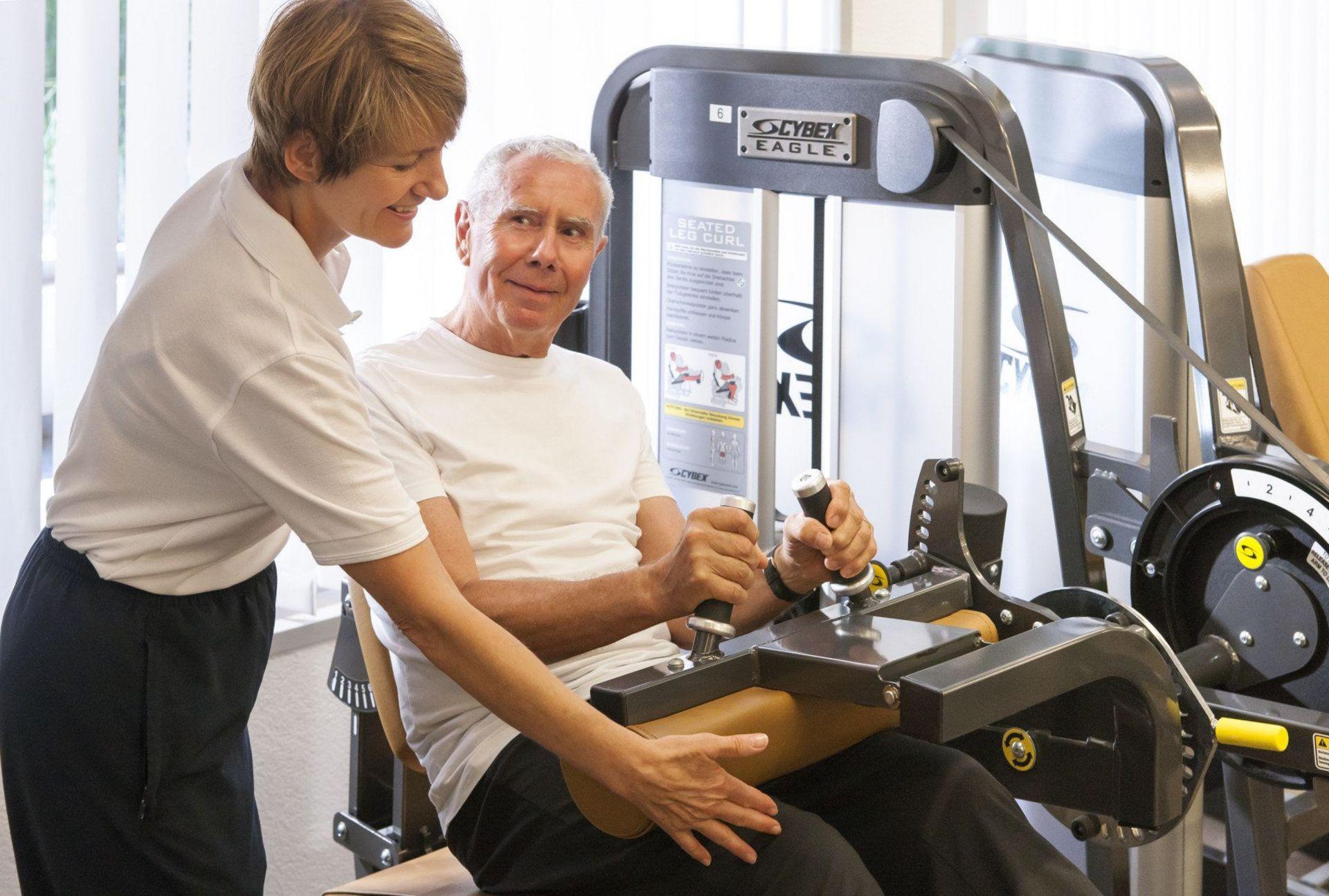 Fitness-Instruktorin unterstützt Senior am Gerät