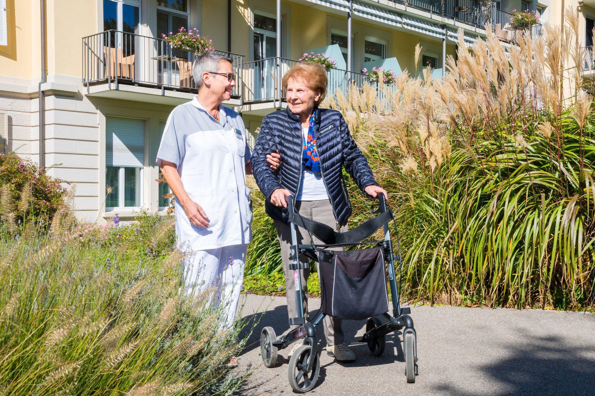 Pflegerin begleitet Patientin mit Rollator durch sonnigen Park