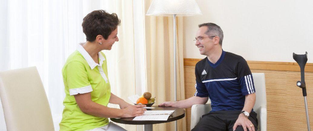 Mitarbeiterin Roomservice bespricht sich mit Patient am Tisch