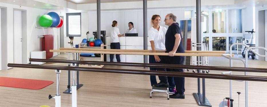 Therapeutin übt mit Patient in MTT-Raum an Geräten