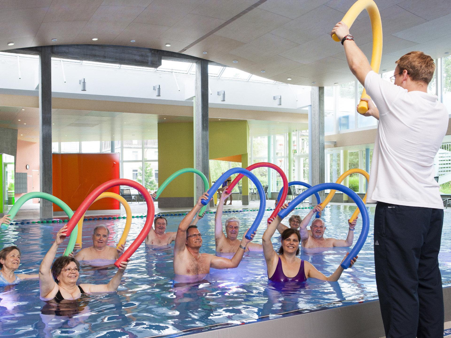 Physiotherapeut zeigt Übung vor Gruppe im Wasser